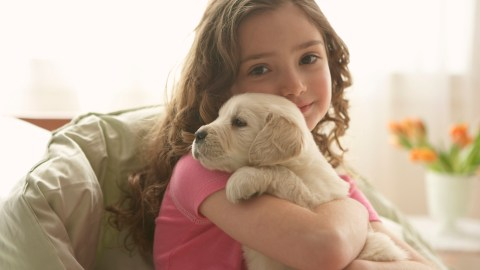 Young child hugging a puppy to help calm anxiety