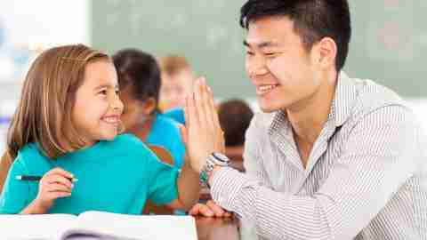 Teacher uses strategies to help ADHD students succeed by acknowledging a student's achievement with a high-five.