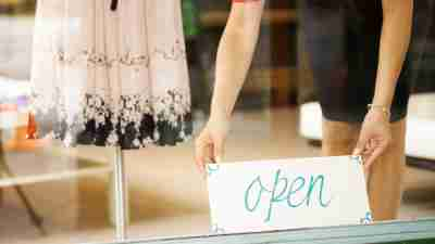 A small business owner with ADHD places a Open sign in her shop window.
