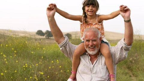 A grandfather holds a young girl on his shoulders — both are the right age for brain imaging.