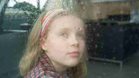 A girl with social anxiety disorder looks out a window