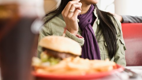A woman with social anxiety disorder talks to a friend at a restaurant.