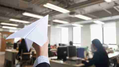 Man procrastinates by throwing a paper airplane in his office. CBT can improve procrastination.