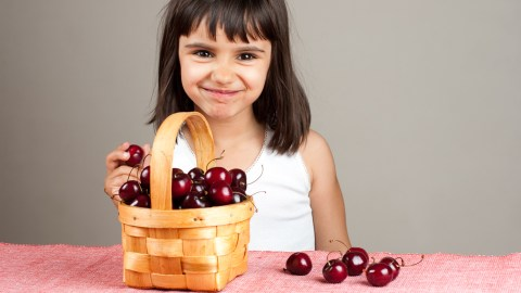 A girl counts a basket of cherries to improve math skills