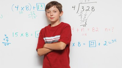 A boy practices math problems on a whiteboard to improve math skills