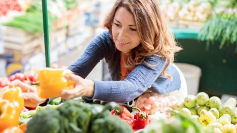 A woman picks out peppers in the grocery store. She knows that eating healthy helps with stress management.