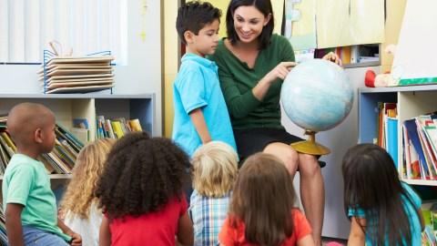 A teacher giving an attention grabbing presentation, a good strategy to improve classroom behavior.