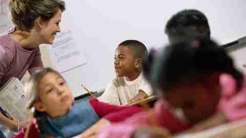 Offering sincere praise, like teacher does for her student, is a great way to improve classroom behavior.