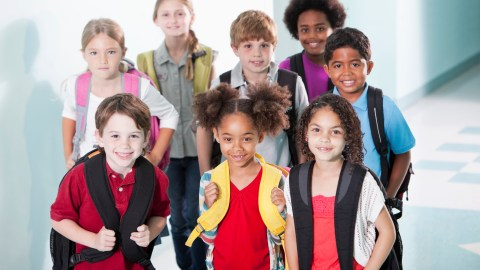A group of young students standing prepared outside their classroom and ready for the new school year.