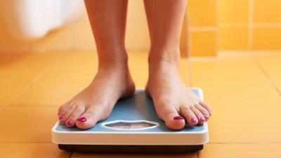 A woman on a scale struggles with ADHD weight loss.