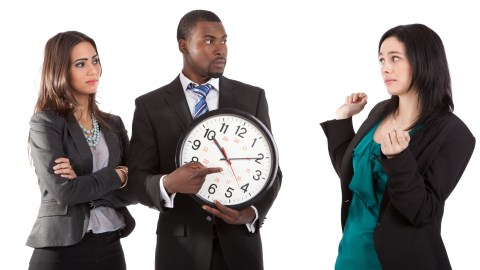 A man points at a clock to remind a woman of how to be on time