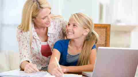 A parent and her daughter work on homework together, helping to relieve homework stress and frustration.
