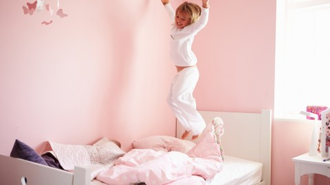 A girl jumping on the bed can't sleep because of her ADHD.
