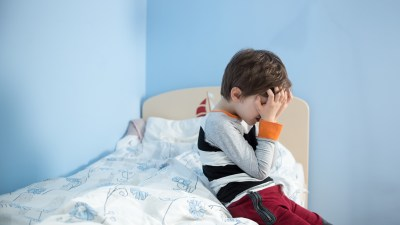 A boy with ADHD sitting on his bed is frustrated because he can't sleep