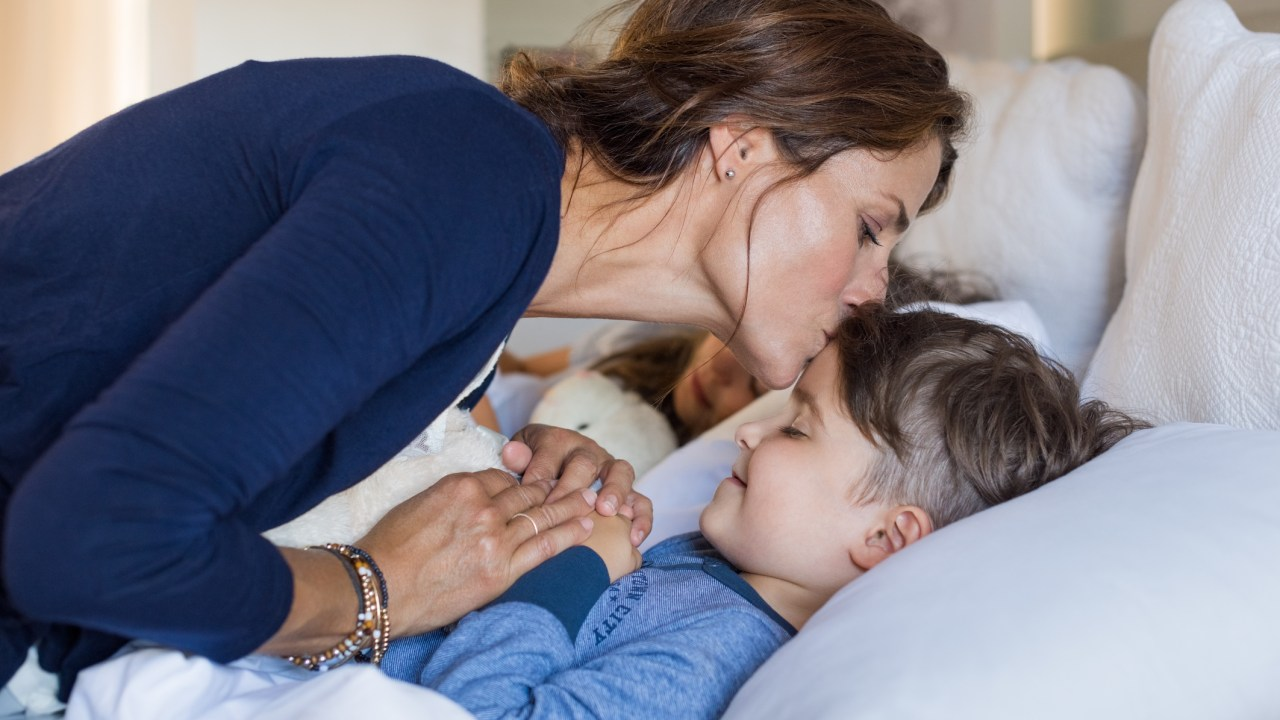 A mom kisses her child with ADHD and sleep problems good night