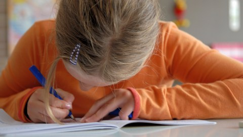 Girl with ADHD practicing writing strategies in school