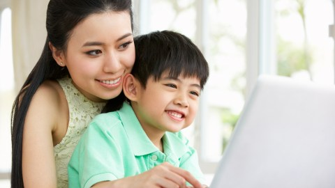 Mother and son looking up ADHD writing strategies on laptop computer