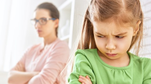 A child with ADHD and oppositional defiant disorder sulks by her mother.