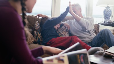 A dad high-fives his child with ADHD. Giving praise is one of his ADHD parenting strategies.