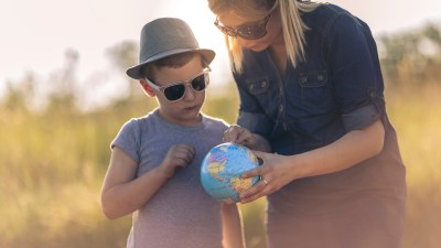 Mom teaches her son geographty outside, advocating for different teaching styles.