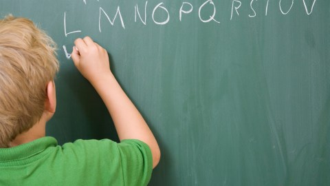 A student with ADHD writes on the chalkboard