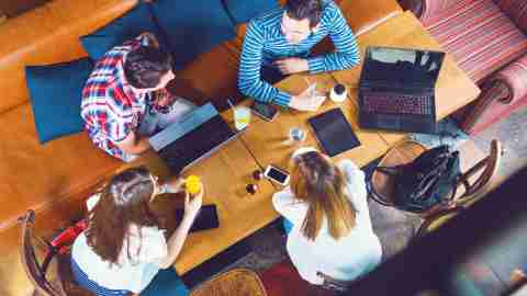 An overhead view of a group of young adults with ADHD discuss why they don't have any friends at a table.