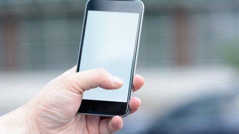 An adult with ADHD holds a smart phone, getting ready to call a friend.