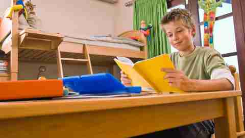 A boy uses ADHD homework strategies to finish reading assignments.