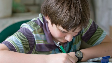 A boy uses ADHD homework strategies to finish his assignments