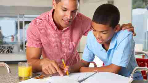 A boy and his father use ADHD homework strategies to finish assignments together.