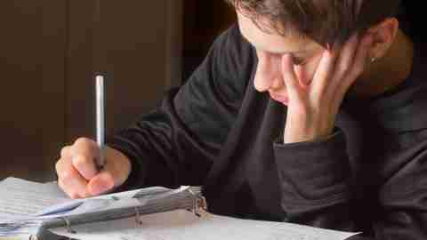 A teen uses ADHD homework strategies to finish his assignments.