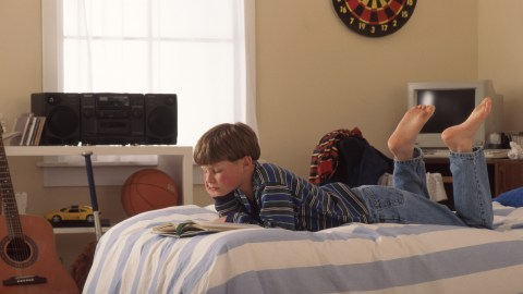 A boy with ADHD lays on his bed, and reads through his daily routine.
