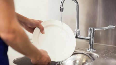A child with ADHD washes the dishes after dinner as part of her daily routine.