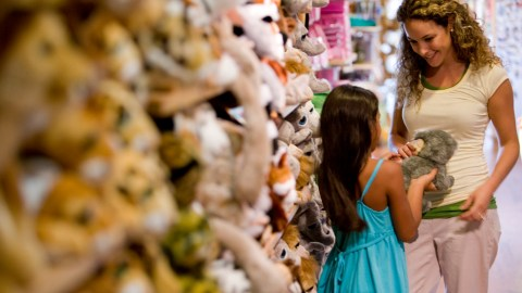 A mother talks with her daughter about anger management in front of a stuffed animal display.