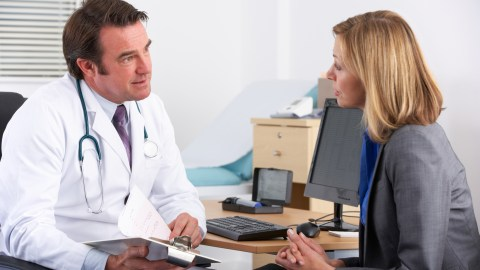 A doctor talking to his patient, asking if she has questions about her ADHD medication