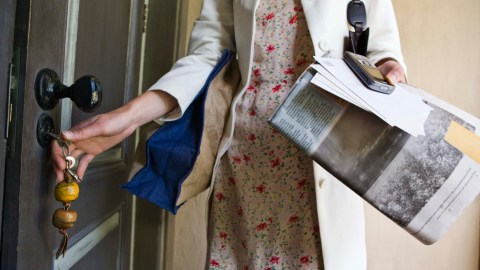 A woman with ADHD opens her front door with junk mail in her hands