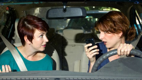An easily distracted woman drives while talking to her friend and texting on her phone.