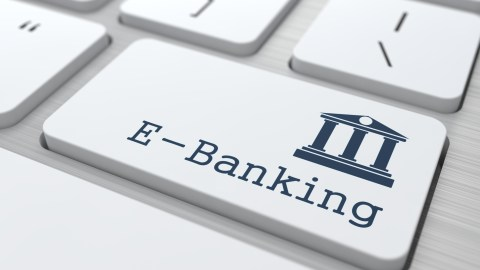 A person with ADHD sets up automatic payments using e-banking to avoid forgetting bills.
