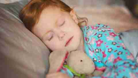 A little girl sleeps in bed. Sleep is key to avoid ADHD tantrums during the day.
