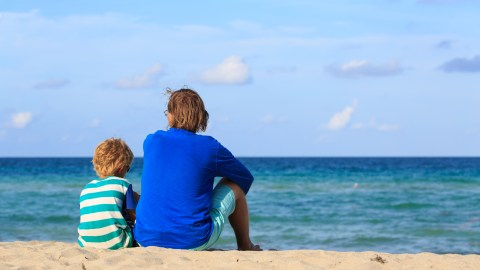 A father and son sit on the beach and talk about what to do when he lies