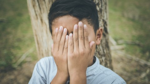 ADHD Boy covers his face because he is ashamed
