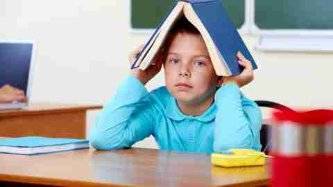 Boy hiding under a book — he's not socially maladjusted, he has ADHD and he's bored.