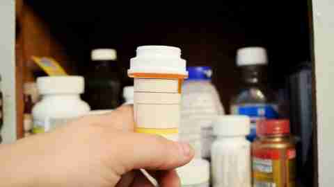 A child reaches for a bottle of pills, despite being shamed for taking ADHD medication.