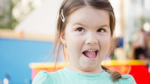 A girl with ADHD makes a funny face because she forgot what she was going to say.