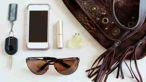 A woman with ADHD puts the contents of her purse on a table: keys, a cellphone, chapstick, and sunglasses
