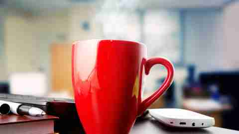 A red coffee cup sits on an office desk, where a person with ADHD set it down and forgot it.
