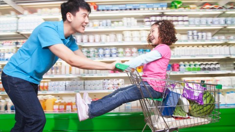 A father pushes his child in the supermarket — even grocery shopping is an adventure.