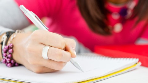 A girl writing and learning how to study with ADHD