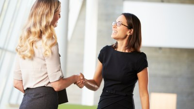 A woman shakes hands with her boss after discussing strategies to succeed at work with ADHD.