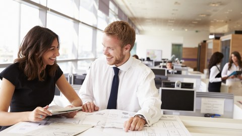 Two coworkers smile and work together, using strategies to succeed with ADHD at work.